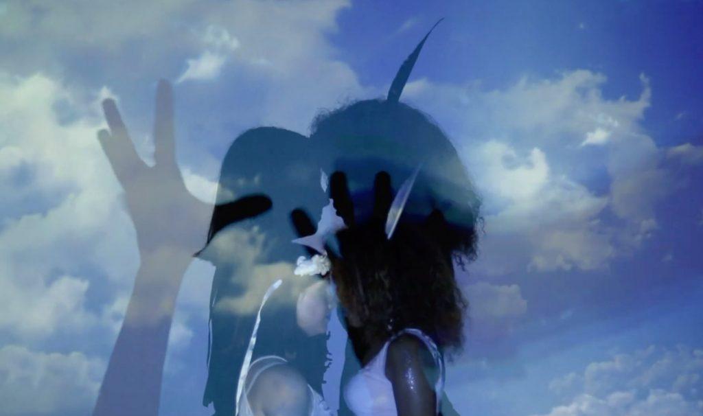 fond de ciel bleu avec des nuages, deux femmes face à face front contre front, avec l'ombre d'une main sur le côté