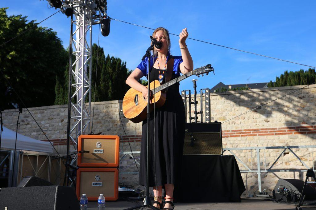 Lucie Joy avec une guitare électrique sur la scène du Cryptoportique de Reims
