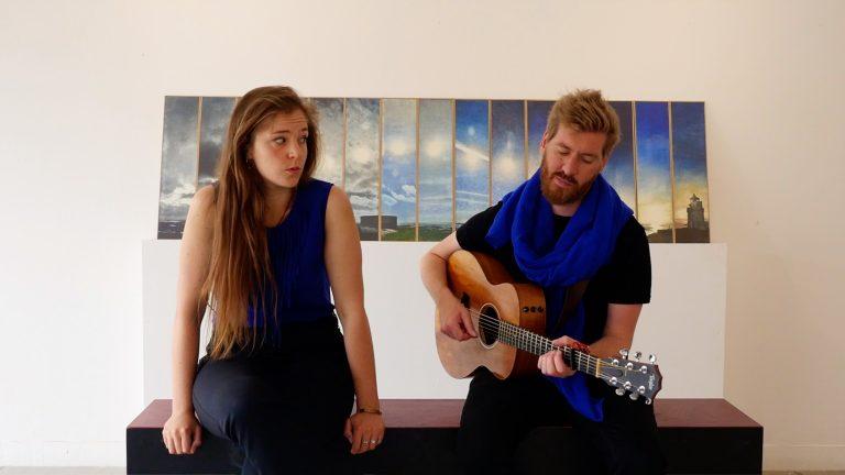 Lucie Joy et Victor Doyen assis, Victor joue de la guitar, Lucie le regarde. Ils jouent Les Gens raisonnables - Mickey 3D