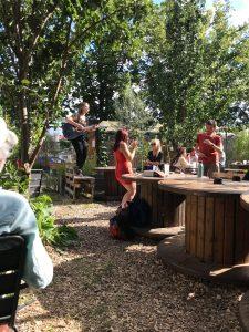 Lucie Joy avec une guitare debout sur une table dehors au Jardin21